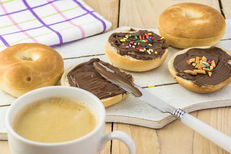 Chiuda in su dei mini bagel freschi con la diffusione della nocciola del cioccolato e la tazza di caffè. Archivio Fotografico - 89370715