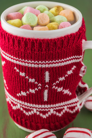 Close up of Christmas cover mug with hot cocoa with milk and colorful marshmallows