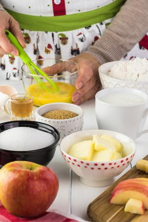 Grandma in Christmas apron whisking eggs for cardamom cognac apple cake.
