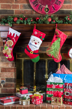 christmas decorations on fireplace with christmas gift boxes christmas socks and fir garland stock