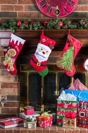 christmas decorations on fireplace with christmas gift boxes christmas socks and fir garland stock