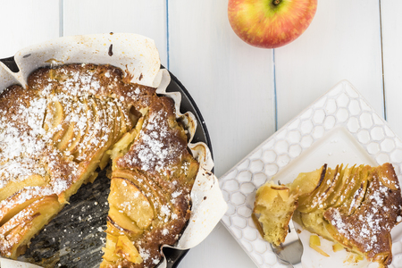 Top view of homemade cut cardamom cognac apple cake in iron skillet. 写真素材