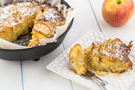 Close up of homemade cut cardamom cognac apple cake in iron skillet.