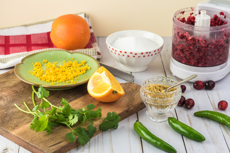 Close up of ingredients for cranberry salsa - orange, cranberries, jalapeno, ground ginger. Фото со стока