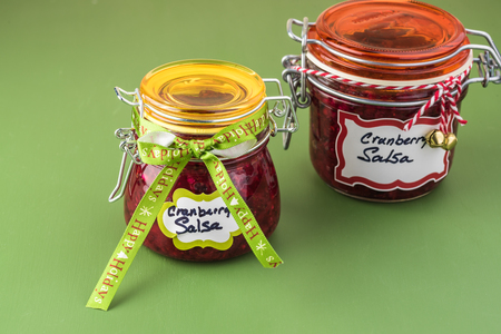 Close up of jars with fresh homemade cranberry salsa decorated for Christmas gifts.
