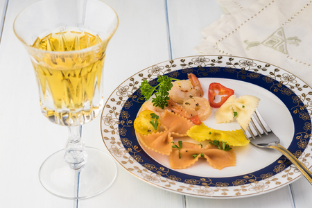 Close up of plate with  shrimp veggie colorful bowtie pasta and glass of wine on wooden background.