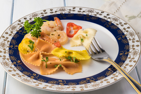 Close up of plate with  shrimp veggie colorful bowtie pasta on wooden background.