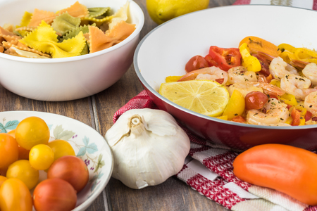 Close up of skillet with fried shrimp and vegetables, boiled bowtie pasta - ingredients for pasta. Stock Photo