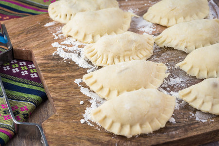 Close up of cutting board with homemade uncooked apple empanadas. Stock Photo