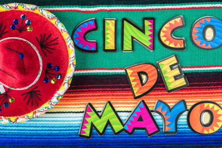 Cinco De Mayo background with colorful mexican poncho serape rug, colorful letters and sombrero.