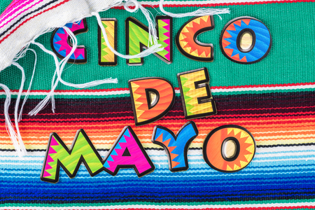 Cinco De Mayo background with colorful mexican poncho serape rug and colorful letters.