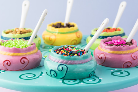Close up of colorful ceramic bowls with assorted topping for ice cream on the wooden stand. Imagens