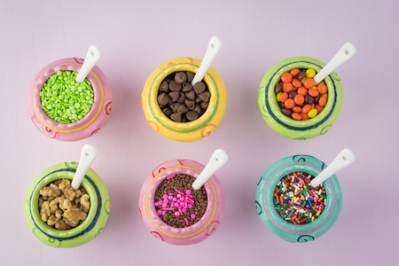 Top view of colorful ceramic bowls with assorted topping for ice cream.