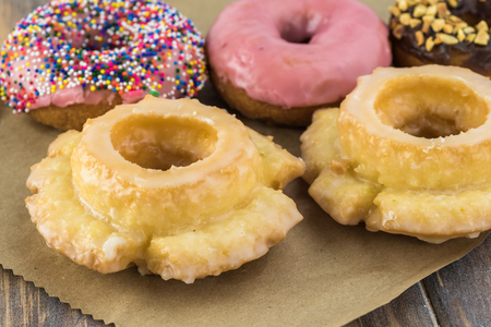 Close up of assorted donuts with clolor of glaze, flavor and sprinkles on wooden background.