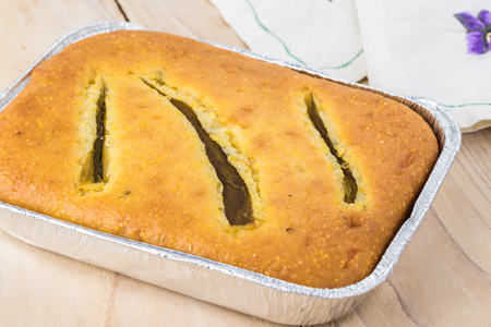 Close up of fresh baked hatch chili pepper cornbread on a wooden background. Banco de Imagens
