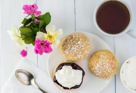 Vista superior de deliciosos bollos ingleses con mermelada de frambuesa, crema cuajada y taza de té. Foto de archivo