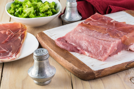 Cut pork loin, bowl with broccoli rabe and prosciutto on wooden background.