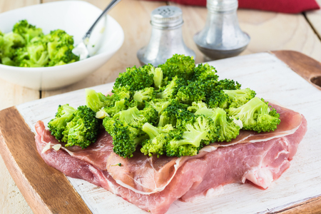 Cut pork loin on cutting board with prosciutto and broccoli rabe on the top - ingredient for stuffed pork. Imagens