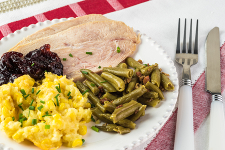 Close up of plate for holiday with pieces of smoked turkey, corn casserole and green beans with bacon.