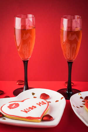 Glasses of wine, plates with heart shaped cookie on a red  background.