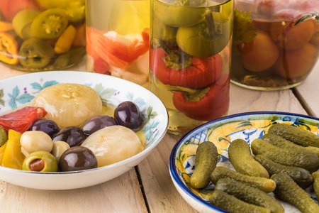 Close up of bowl with mixed vegetables in sunflower oil, bowl with marinated cornichons  and glass jars with pickled vegetables on the background.