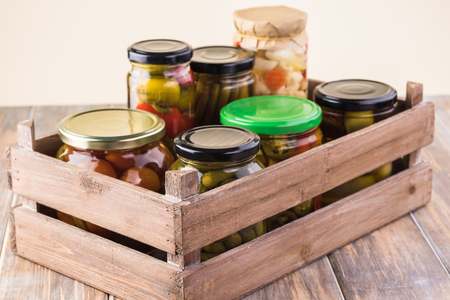 Close up of crate with variety of pickled vegetables in glass jars.