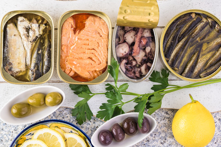 Close up of varieties of open  canned fish. Tin cans with smoked salmon fillets, sardines, calamari, sprats.
