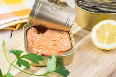 Open  canned fish. Tin can with smoked salmon fillets.