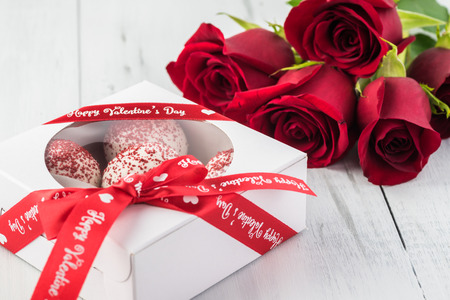 Close up of box with mini cakes and red roses - gift for Valentines Day. Greeting card concept.