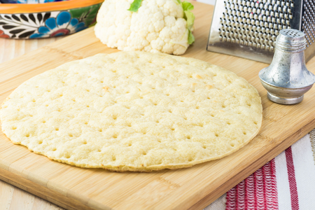 Close up of cauliflower pizza crust on a cutting board. Imagens - 116597207