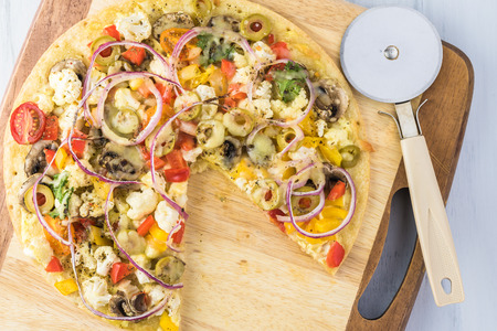 Fresh baked, cut piece, homemade cauliflower crust pizza with assorted vegetables. Reklamní fotografie - 116597210