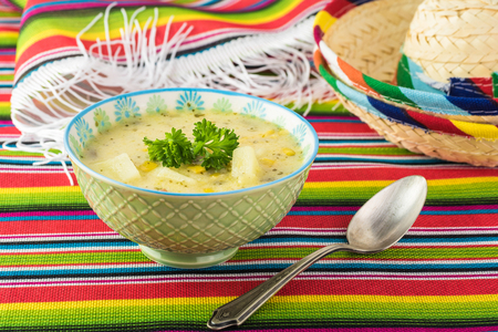 Bowl with Fiesta ham soup on a table decorated for Fiesta celebration with mexican table runner, sombreros.