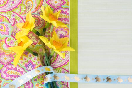 Easter greeting card concept. Spring flowers decorated with bunny ribbon. Copy space.