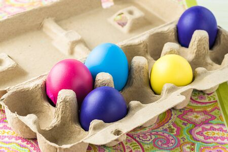 Close up of colorful painted eggs in box.