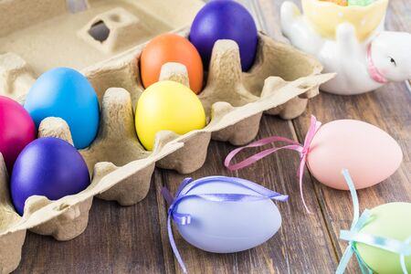 Close up of colorful painted eggs in box on a wooden background. Stock Photo