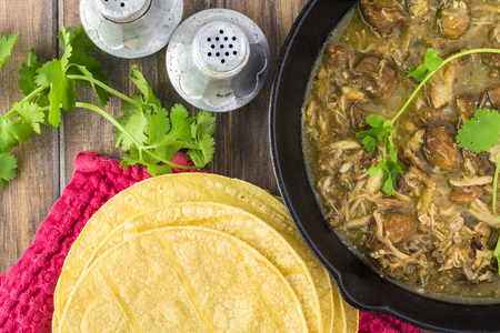 Close up of corn tortillas and iron skillet with pork in chile verde.