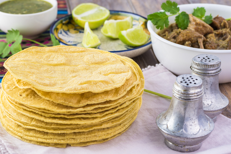 Close up of corn tortillas and bowl with pork in chile verde. Stock fotó