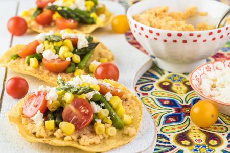Close up of veggie tostadas with cauliflower mash on a cutting board.