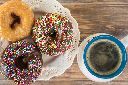 Close up of fresh assorted donuts and a cup of coffee for Fathers day.