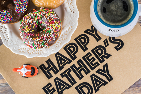 Greeting card with assorted donuts and cup of coffee for Fathers day.