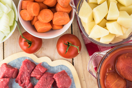 Ingredients for hungarian soup goulash: pieces of beef, onion, carrot, potatoes, bell pepper, peeled tomatoes in tomato juice.