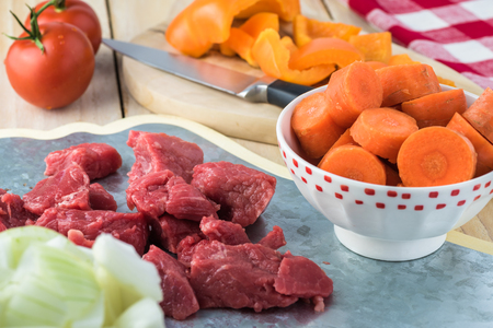 Ingredients for hungarian soup goulash: pieces of beef, onion, carrot, bell pepper.