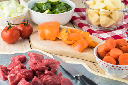Ingredients for hungarian soup goulash: pieces of beef, onion, carrot, potatoes, bell pepper, zucchini.
