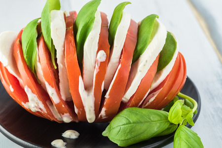Close up of multilayer tomato mozzarella basil healthy sandwich on black plate. 스톡 콘텐츠