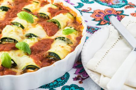 Fresh baked of zucchini rollups with cheese in marinara sauce.