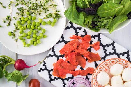 Close up of ingredients for healthy salad with smocked salmon - baby greens, cherry tomatoes, radish, green peas, smocked salmon, mozarella cheese and broccoli shoots.