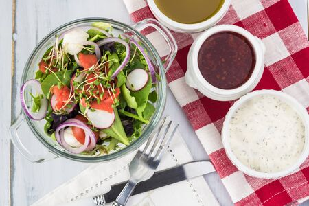 Close up of glass bowl of healthy  salad with smocked salmon and choice of dressings. Stock Photo