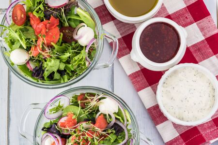 Close up of glass bowls of healthy  salad with smocked salmon and choice of dressings. Stock Photo