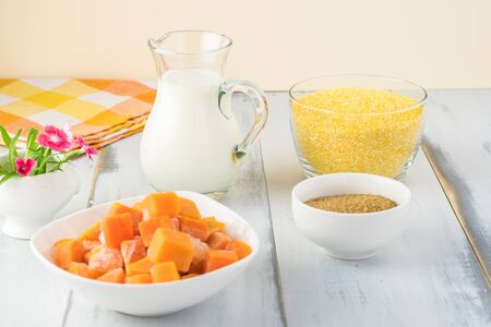 Close up of ingredients for organic polenta with milk and pumpkin - coarse ground cornmeal, frozen pieces of pumpkin,  milk and brown sugar. Stock Photo