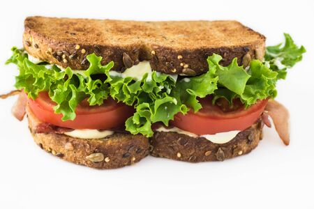 Close up of BLT sandwich with bacon, tomatoes, lettuce and myonnaise.